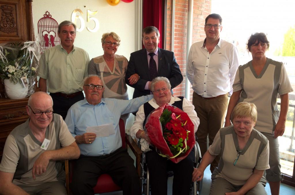 Foto De jubilarissen met dochter Lilly, burgemeester Luc De Ryck, OCMW-voorzitter Werner Maerevoet, directeur Jean-Paul Elegeert en personeelsleden.