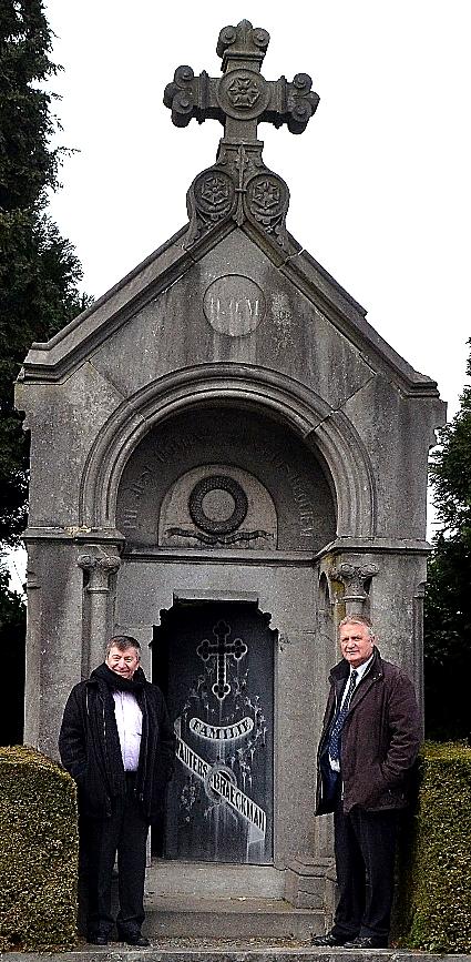 Burgemeester Luc De Ryck en schepen Hugo Maes, bevoegd voor begraafplaatsen, poseren aan de grafkapel van Wauters-Braeckman.